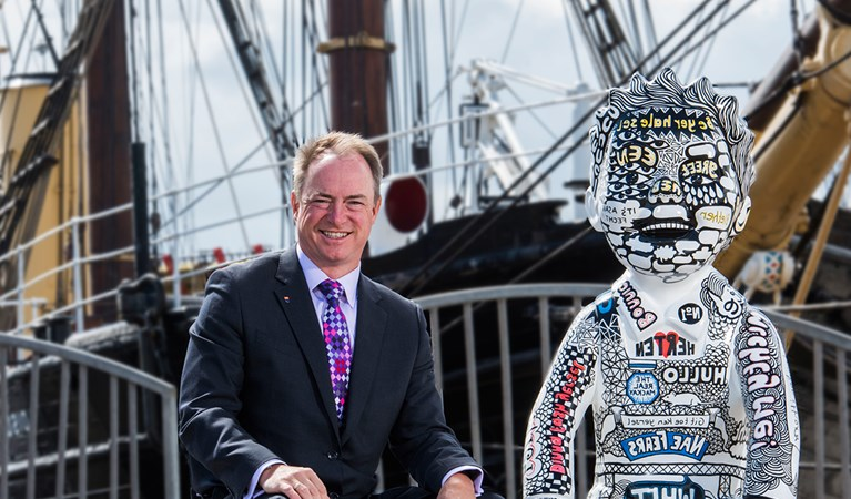 Andy Lothian sitting with the Insights sponsored Oor Wullie outside the Discovery ship.