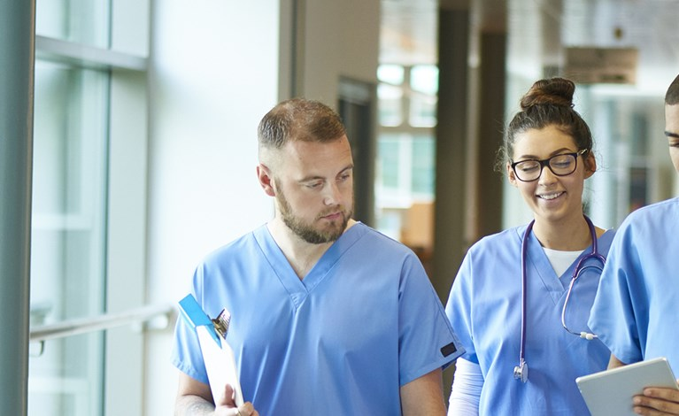 Three junior doctors walking along a hospital corridor discussing case and wearing scrubs. A patient or visitor is sitting in the corridor as they walk past.