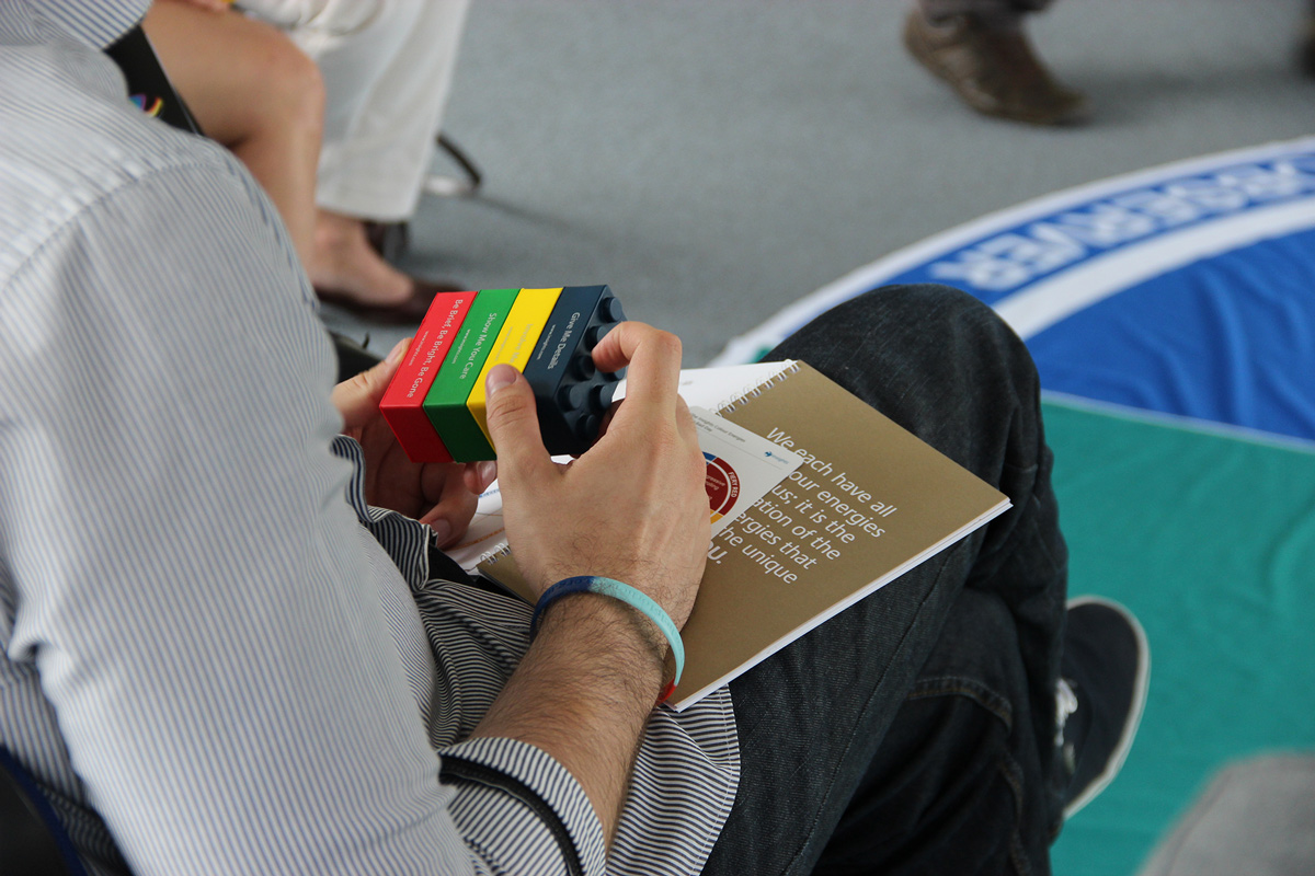 Man holding the colored bricks in a workshop