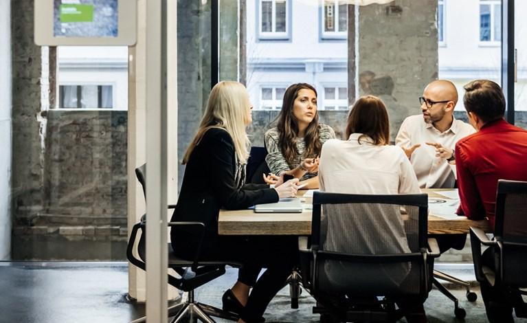 Un gruppo di persone è seduto a un tavolo durante una riunione d'affari in un luminoso ufficio moderno.