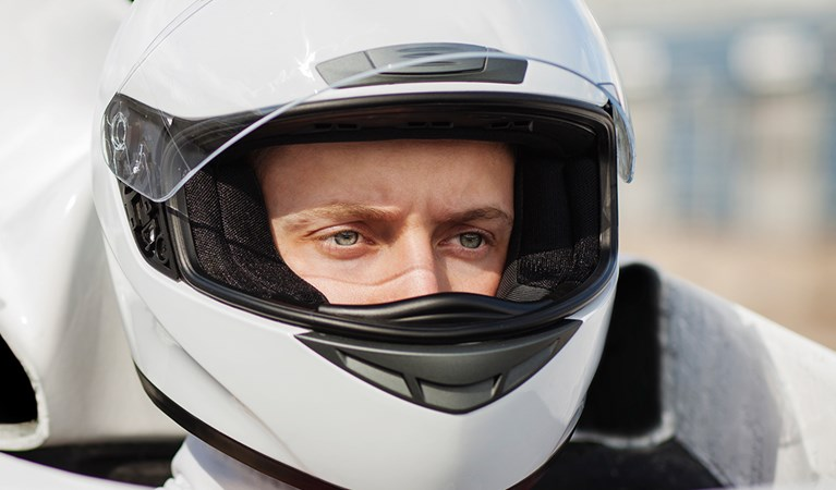 Close up of racing driver wearing a white helmet