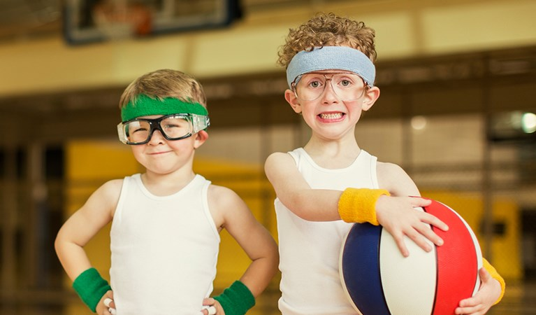 Two geeky children playing basketball