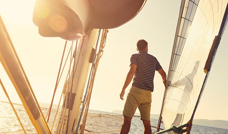 Man standing on a sailing boat out at sea