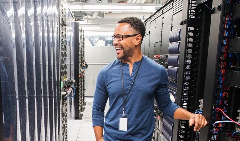 Technicien de rire dans la salle des serveurs informatiques